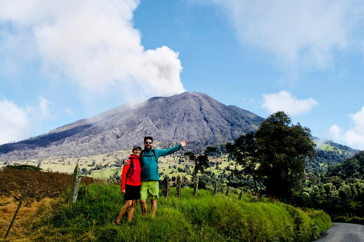 zwei Menschen vor dampfenden vulkan in grüner wiese