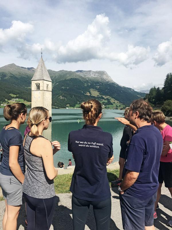 Gruppe von Menschen vor einem See mit einem Kirchturm im Wasser.