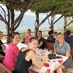 Sechs Personen an einem Essenstisch unter einer Laube