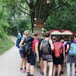 Gruppe Menschen steht vor Theke mit Getränken im Wald