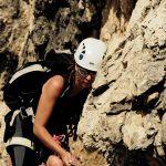 Eine Frau mit dem Kletterhelm Elios auf einem Klettersteig, konzentriert. ©unsplash