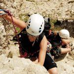 Eine Frau mit Kletterhelm Elios beim Klettern an einem Klettersteig. ©unsplash