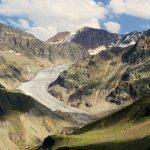 Gräuliche Gletscherzunge zwischen grünen und grauen Felshängen.