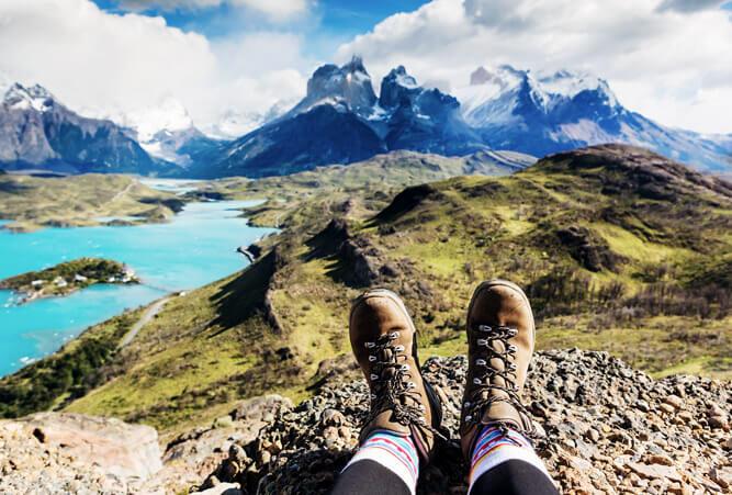 Mädchen-Wanderstiefel und Ausblick auf die Berge von Los Cuernos in Patagonien, Chile