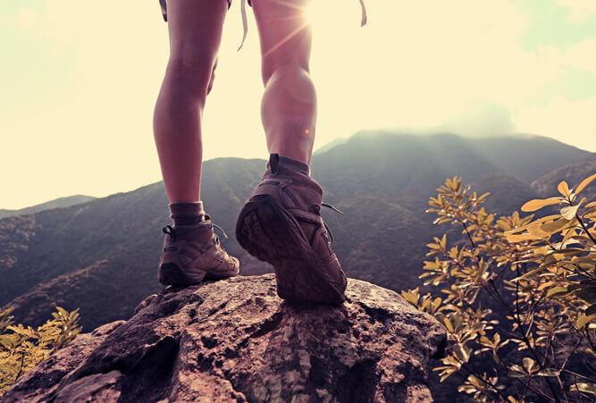 Beide einer Frau, die auf dem Felsen eines Berggipfels steht.