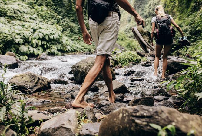 Mann und Frau, die im Wald mit den Schuhen in der Hand den Bach barfuß überqueren.