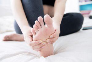 Nahaufnahme von Frauenhänden, welche den rechten Fuß massiert