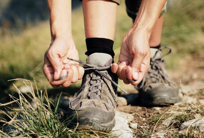 Zwei Frauenhände beim Schnüren von Trekkingschuhen