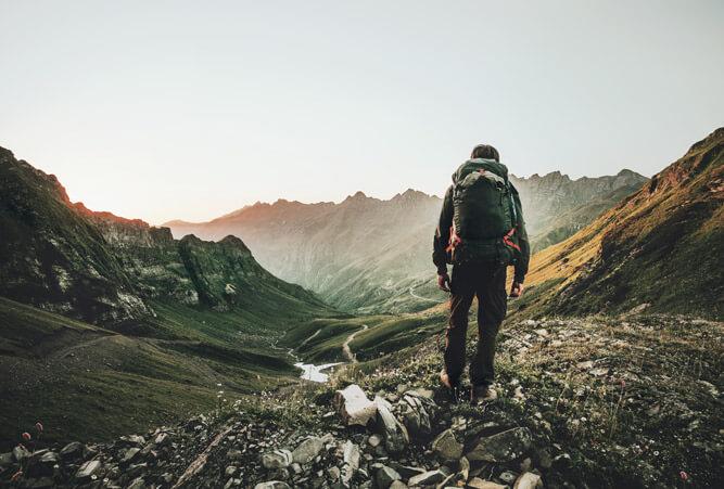 Mann wandert bei Sonnenuntergang im Sommer allein durch die Bergwildnis