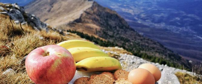 Obst, Brot und Eier auf einem Gipfel. Blick ins Tal