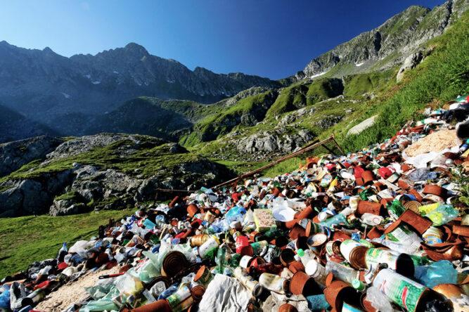 Große Mengen an leeren Plastikflaschen und Müll auf grünen Bergwiesen