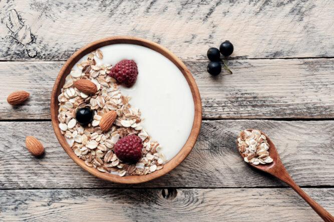 Schüssel mit Haferflocken, Joghurt, Nüssen und Früchten von oben auf einem Holztisch