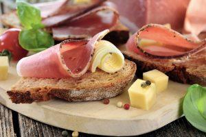 Ein Holzbrett mit Speck, Käse und Brot darauf