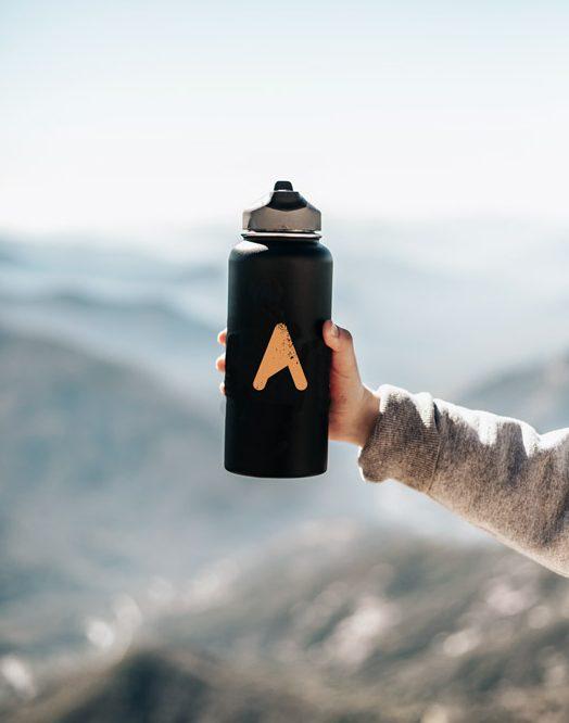 Eine Wasserflasche mti dem ASI Logo in einer Hand. Im Hintergrund sind Gipfel zu sehen.