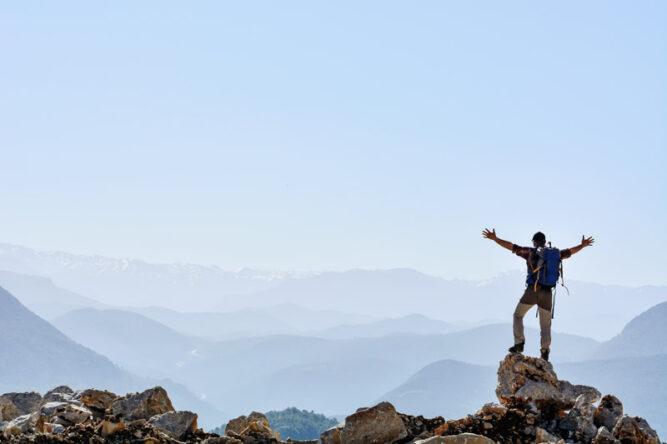Mann mit ausgebreiteten Armen auf Gipfel, hellblauer Himmel