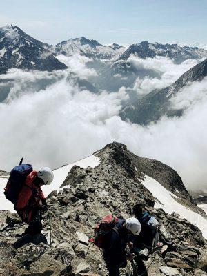 Bergsteiger mit Helm am Gipfel, Schweiz