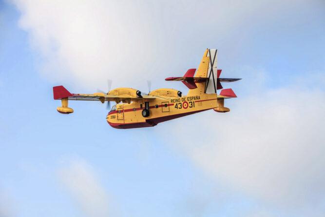 Gelb-rötliches Flugzeug vor bewölktem Himmel.