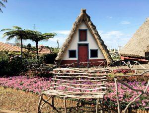 Traditionelles Haus mit Blumen und Holzbank