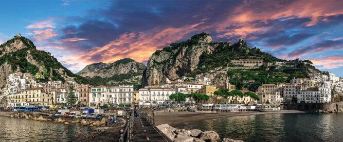 Panorama auf Küstenstadt Amalfi. Sonnenuntergang mit gelb und rot leuchtenden Wolken