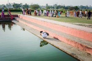 Eine Frau kniet vor einem smaragdgrünen Wasserbecken.