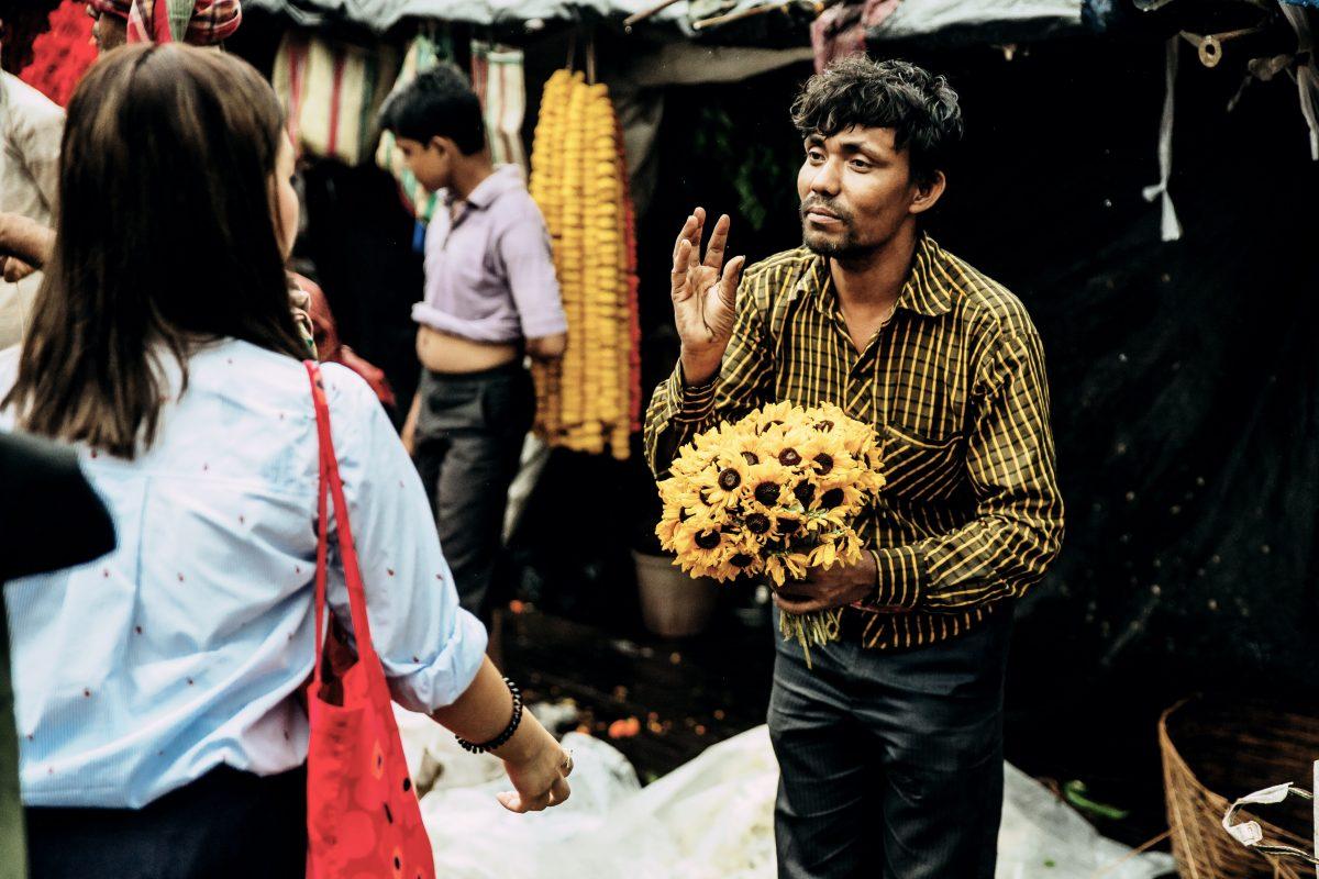 Ein Blumenverkäufer, der mit einer Frau spricht.