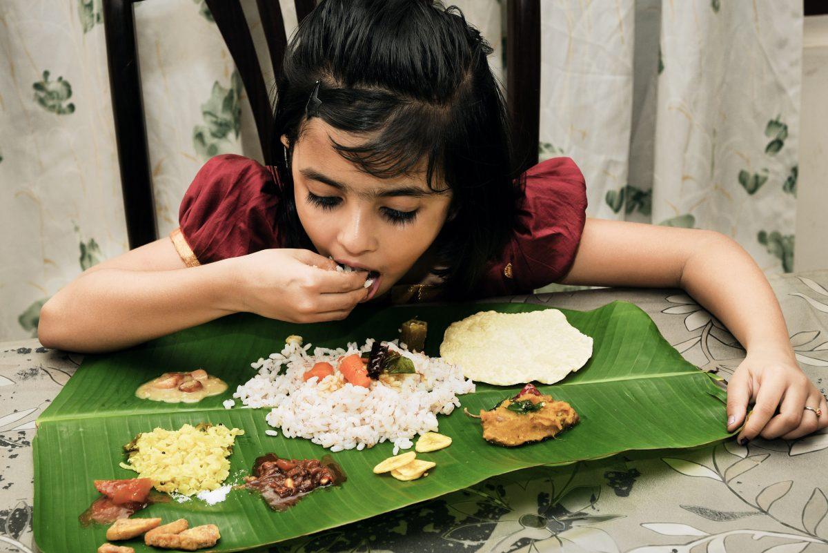 Ein Mädchen isst indisches Essen von einem Bananenblatt.
