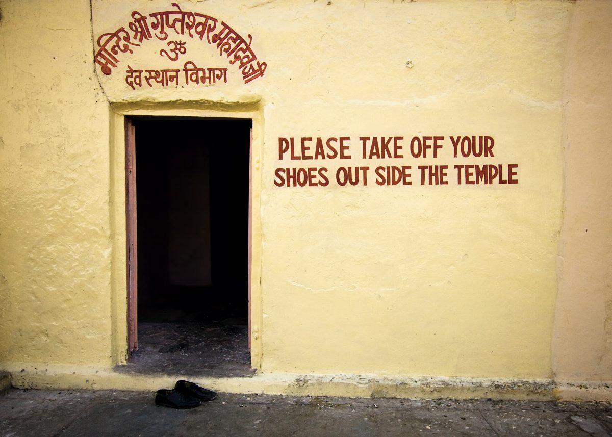 """Ein paar Schuhe vor einem Tempel in Indien mit der Aufschrift """"Bitte Schuhe ausziehen""""."""