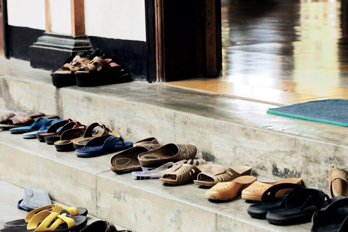 Eine volle Treppe mit Schuhen vor einem Tempel.