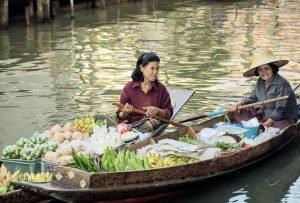Zwei Frauen auf zwei Booten, die mit frischem Obst und anderen Lebensmitteln befüllt sind.