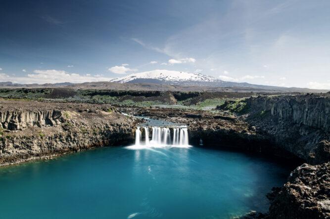 Wasserfälle uns azurblauer See im Vordergrund, Vulkan mit Schneedecke im Hintergrund, Island.
