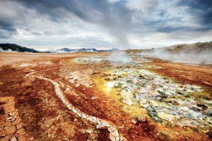 Gelbe und goldrote Gesteinsfläche mit dampfenden Quellen