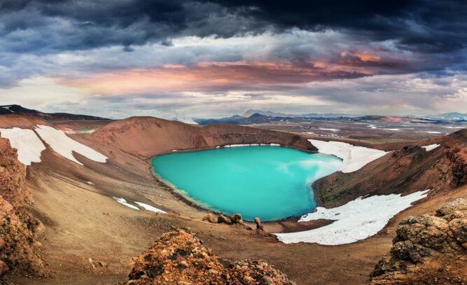 Kleiner helltürkiser See in einem Krater, Schneefelder. Viti Krater, Island.