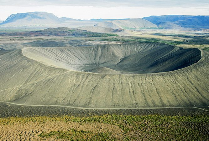Großer Krater in trockener, grünlicher Landschaft, Island, Vulkan.
