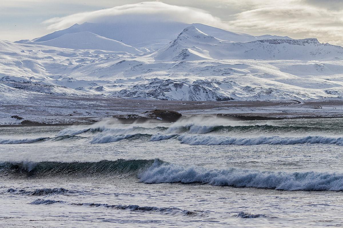 meer mit wellen, verschneite berge im Hintergrund
