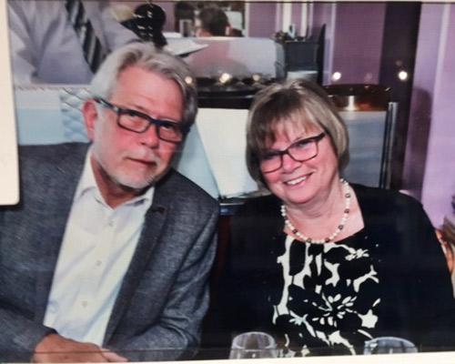 Zwei ältere Personen mit Brillen lächeln von einem Foto.