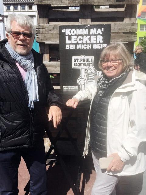 Zwei ältere Personen vor einem Schild