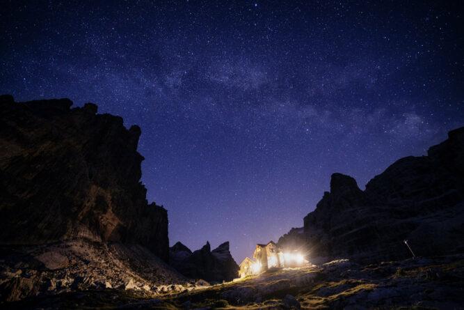 Offener Sternenhimmel über Gebirge, beleuchtete Hütte.