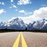 Leere Straße mit atemberaubenden Blick auf die Berge im Grand Teton Nationalpark. © Jesse Collins