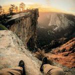 Mann sitzt auf dem Boden und blickt in den Sonnenuntergang im Yosemite Nationalpark, USA. © Jordan Pulmano
