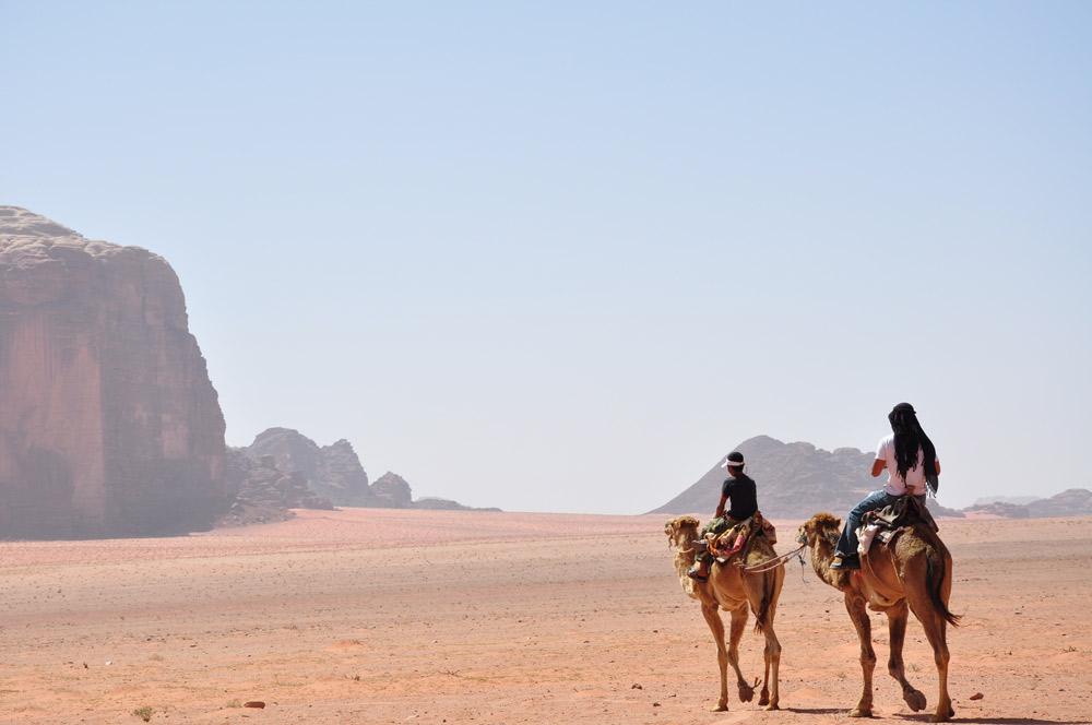 zwei Menschen sitzen auf Kamelen mit wüste und blauem himmel