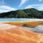 Rot-blauer See mit Wald im Yellowstone Nationalpark. © Jyoti Mann