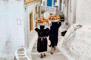 Frauen tragen das Ostergebäck, Tsoureki, auf dem Kopf durch das Dorf, Griechenland