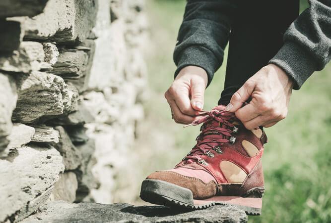 Hände einer Frau, die während einer Wanderung ihre Schuhe auf einen Stein schnürt