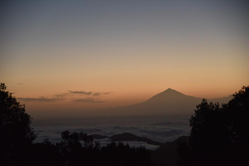 sich orange färbender himmel am horizont, silhoutte von berg davor