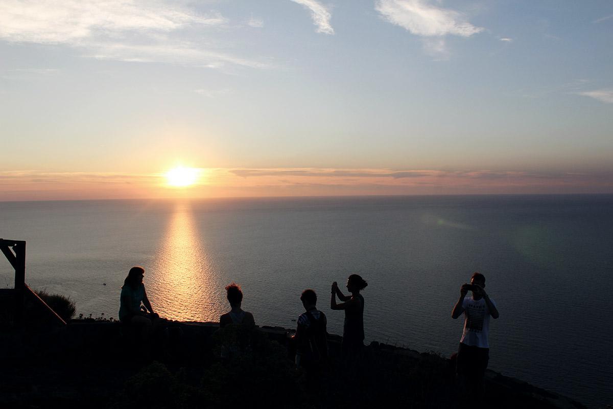 untergehende Sonne am Horizont, davor meer und silhouetten von menschen