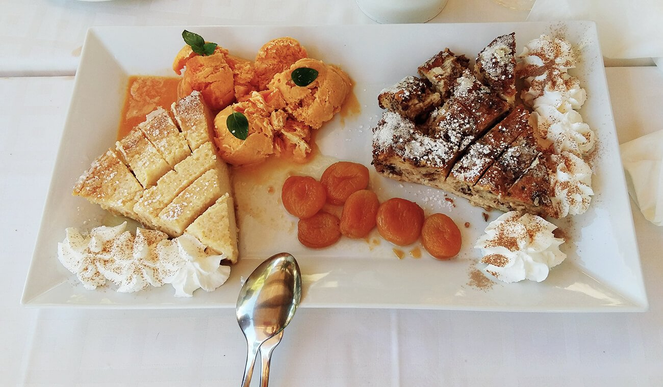 teller gefüllt mit kuchen, eis, weißer sahne und orangenen aprikosen