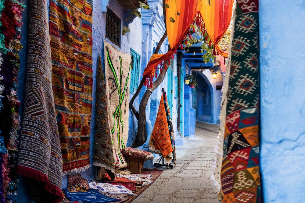 bunte Teppiche an blauer Wand in enger Gasse