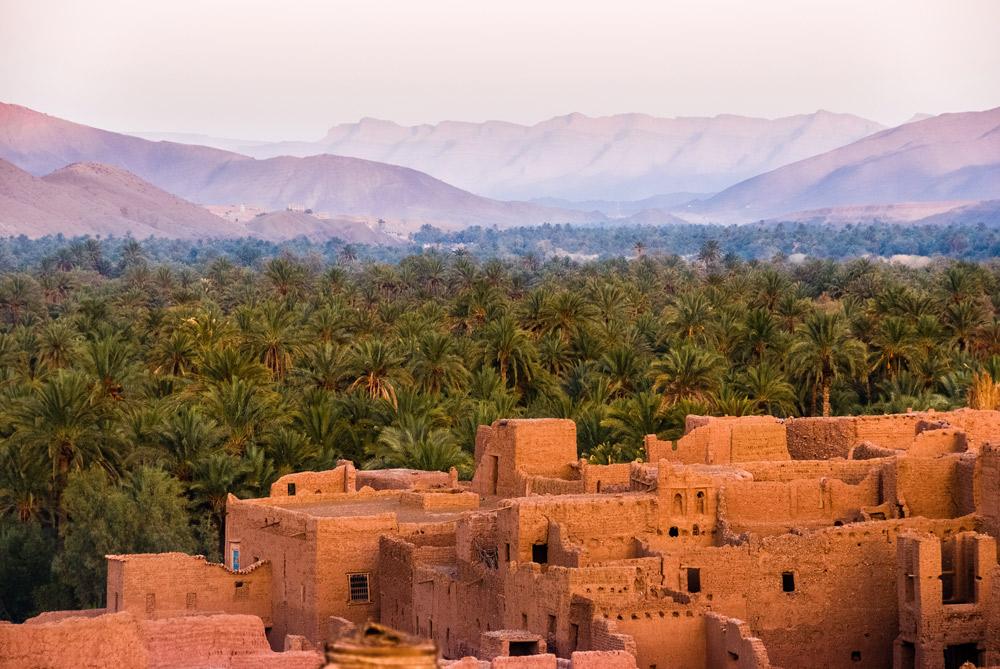 orange Gebäude vor Palmen und Berge im Hintergrund
