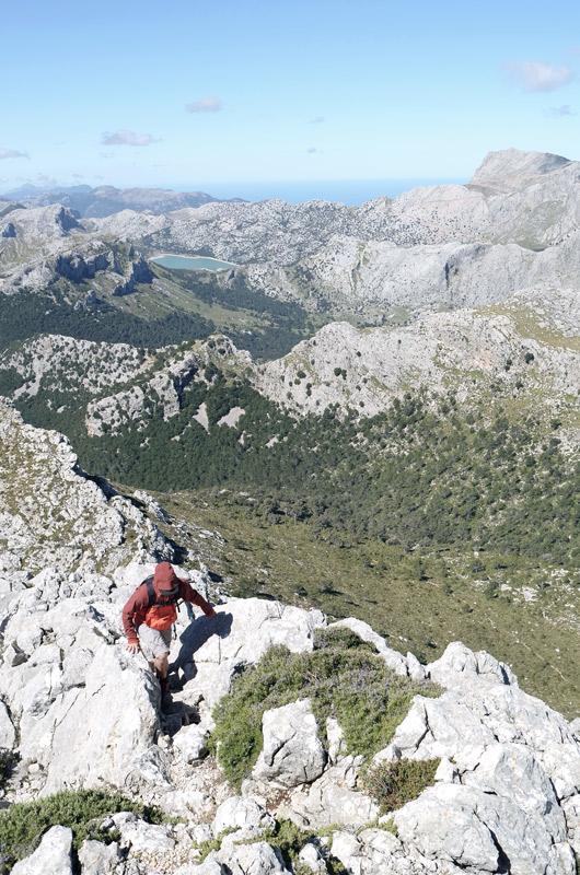 Wanderer in roter Jacke auf felsigem Bergsattel. Ausblick in die Ferne zu einem See und zur Küste. Blauer Himmel