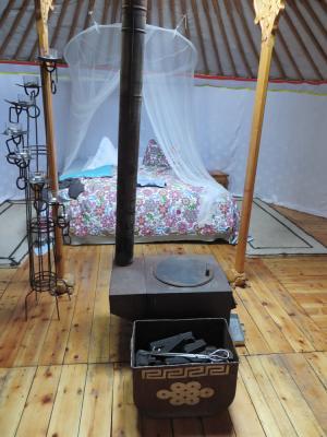 Ofen auf Holzboden und Bett im Hintergrund